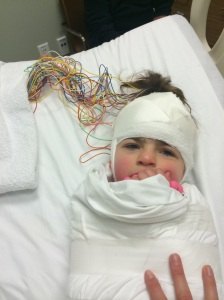 E getting  her EEG on her brain waves to track seizure activity last Friday.  Even in her misery of being wrapped up like a burrito she showed she could find a reason to smile.
